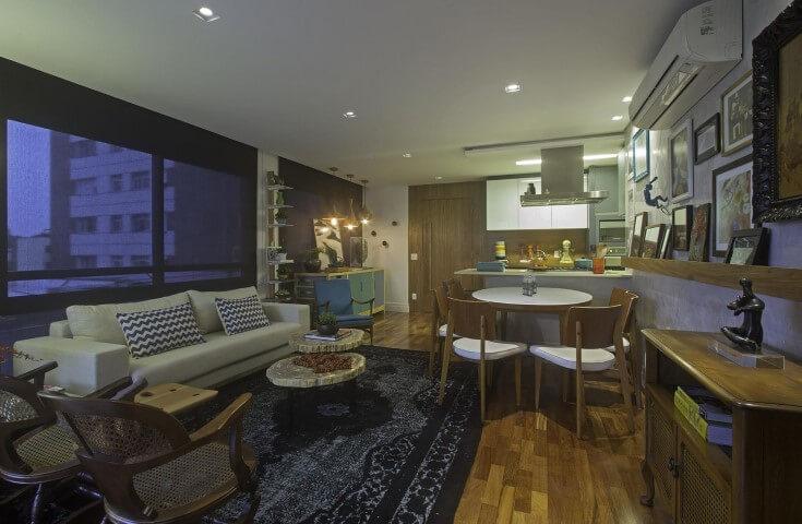 Sala de estar com mesa redonda de madeira branca com cadeiras de madeira Projeto de Negrelli e Teixeira