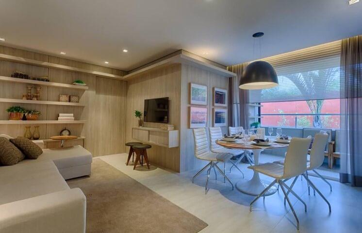 Sala de estar com mesa redonda de madeira e cadeiras brancas Projeto de Renata Basques