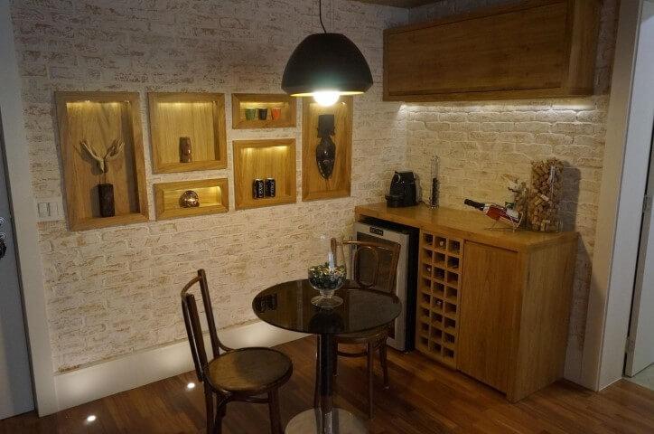Sala de estar com mesa redonda pequena preta com cadeiras de madeira Projeto de Jaqueline Salvador