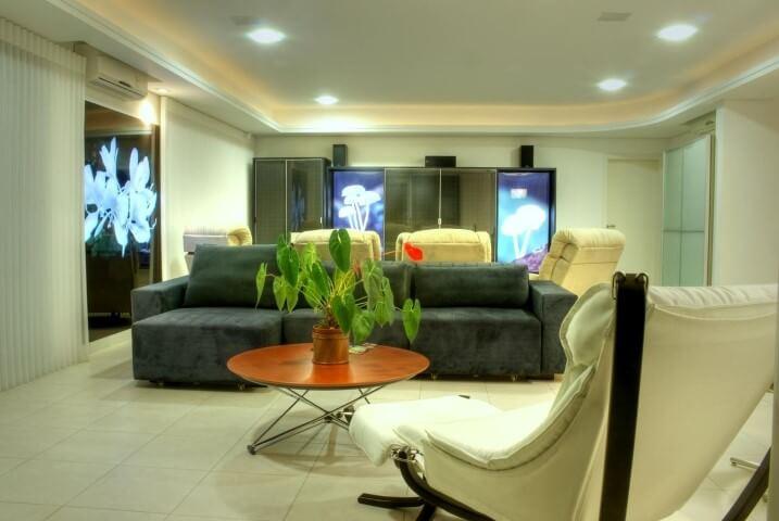 Sala de estar com sofá retratil cinza e poltronas claras Projeto de Braescher Fotografia