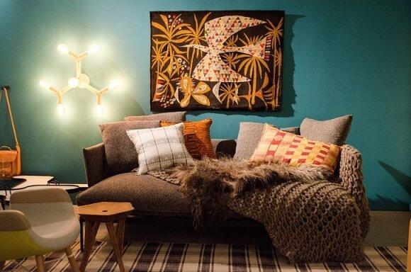 Sala de estar turquesa com sofá marrom com manta de tricô Projeto de Casa Cor SP 2017