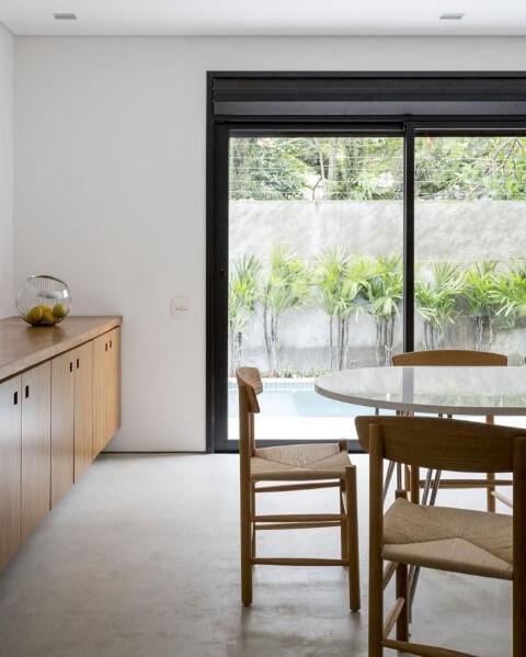 Sala de jantar com mesa redonda branca e cadeiras de madeira Projeto de Felipe Hess