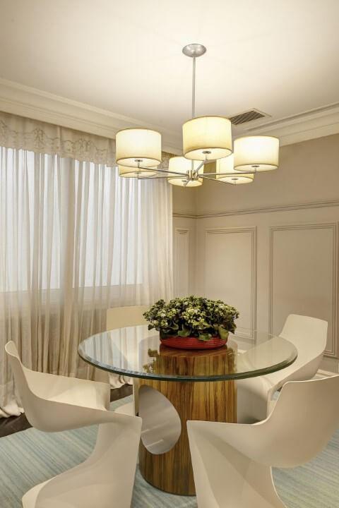 Sala de jantar com mesa redonda de vidro e base de madeira e tapete retangular Projeto de Oscar Mikail