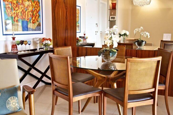 Sala de jantar com mesa redonda de vidro e pés em madeira