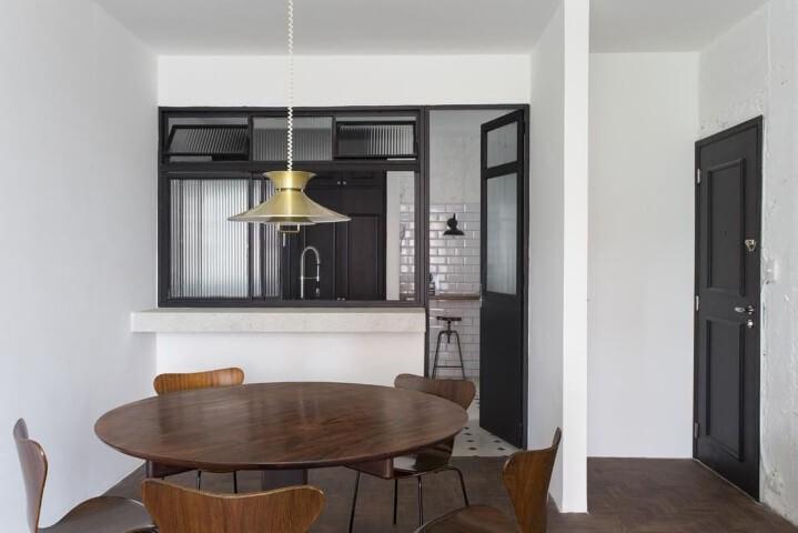 Sala de jantar com mesa redonda e cadeiras de madeira Projeto de Felipe Hess