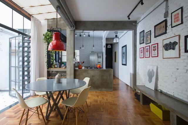 Sala de jantar com mesa redonda preta e cadeiras cinzas em ambiente moderno Projeto de Daniel Winter