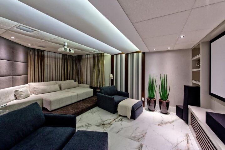 Sala de televisão com sofá retrátil branco e poltronas azuis Projeto de Espaço do Traço