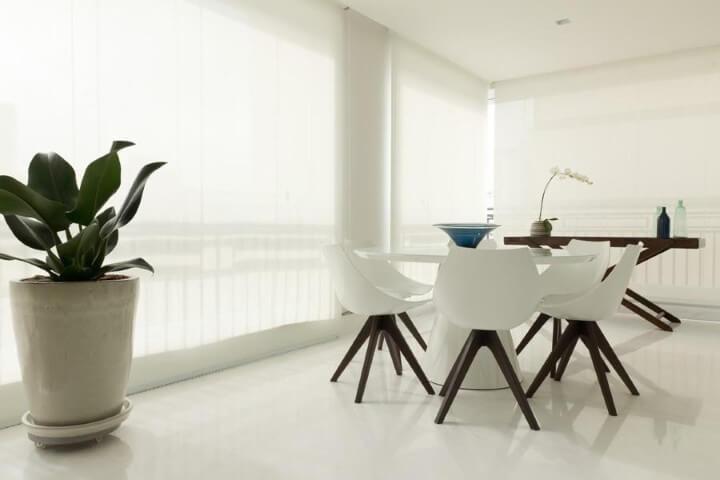 Varanda com mesa redonda e cadeiras brancas Projeto de Marilia Veiga