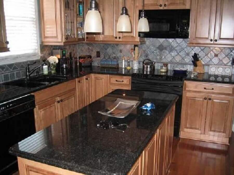 cozinha com granito preto aracruz e armários de madeira