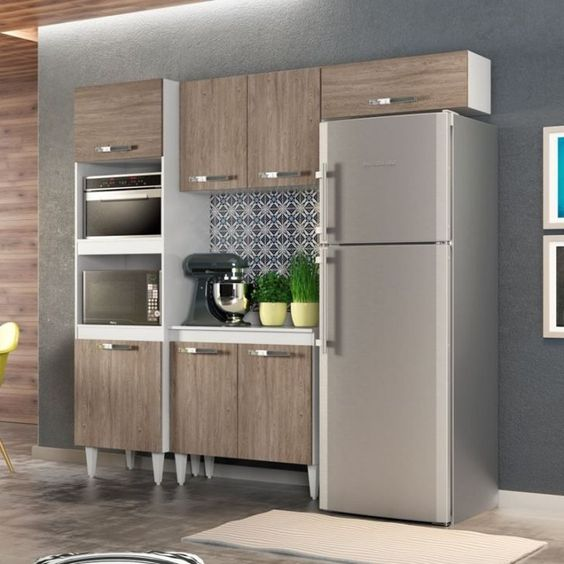 A cozinha modulada com armários marrom e eletrodomésicos em inox também é incrível