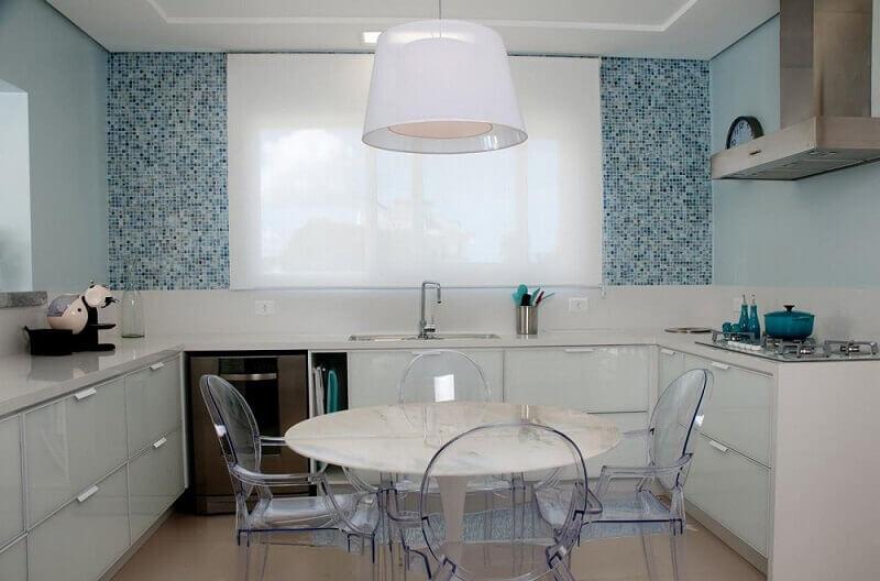 decoração clean com pastilhas azuis para cozinha com cadeiras de acrílico e armário de cozinha modulado