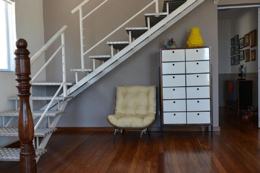 decoração embaixo da escada com poltrona e armário