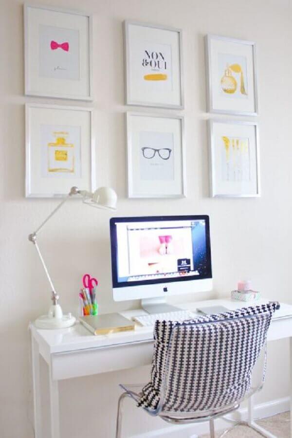 decoração toda branca com escrivaninha simples pequena e quadros na parede