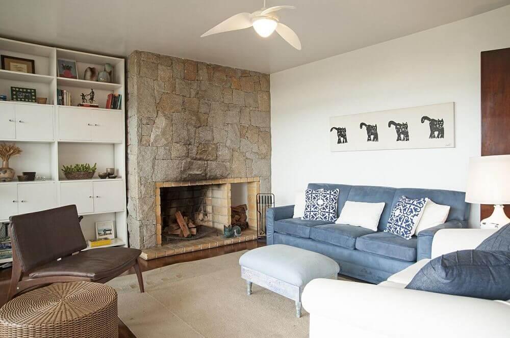 decoração lareira a lenha e sofá azul na sala de estar