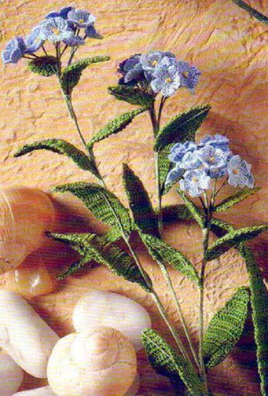 delicado arranjo com flores azuis e folhas em crochê