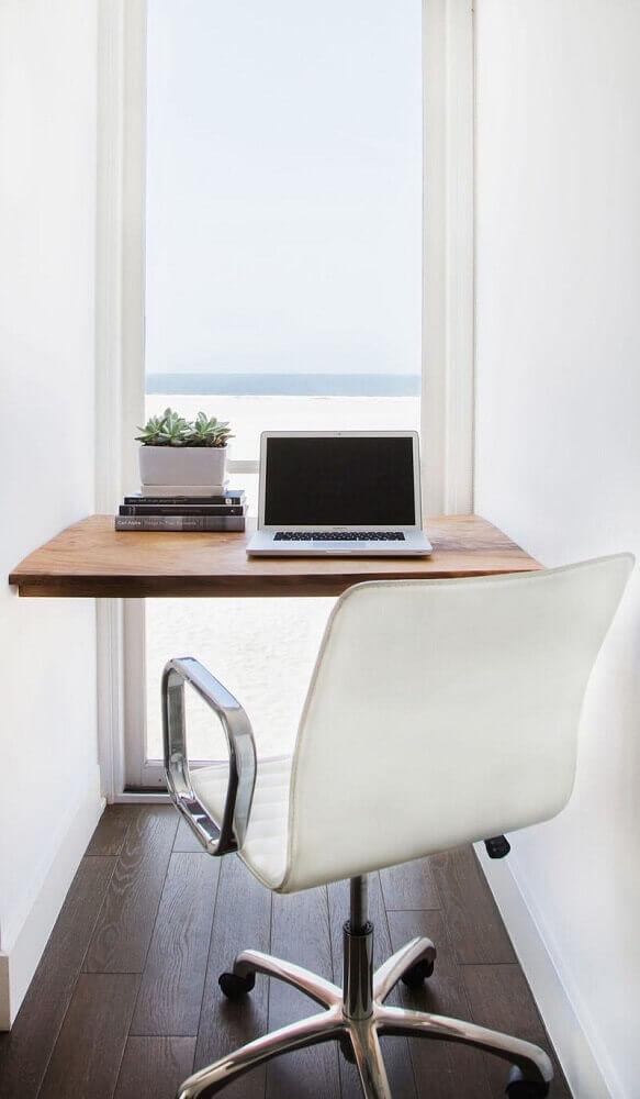 home office pequeno com bancada de madeira e grande janela