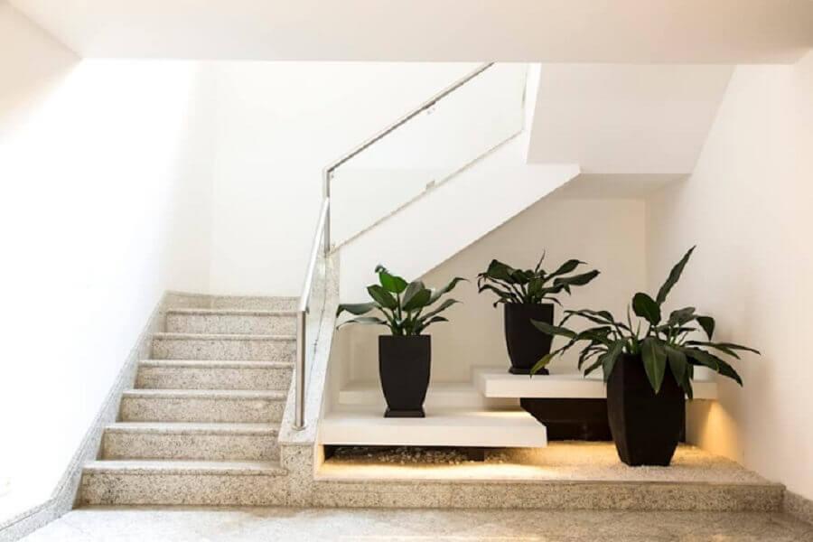 jardim embaixo da escada com vasos de flores