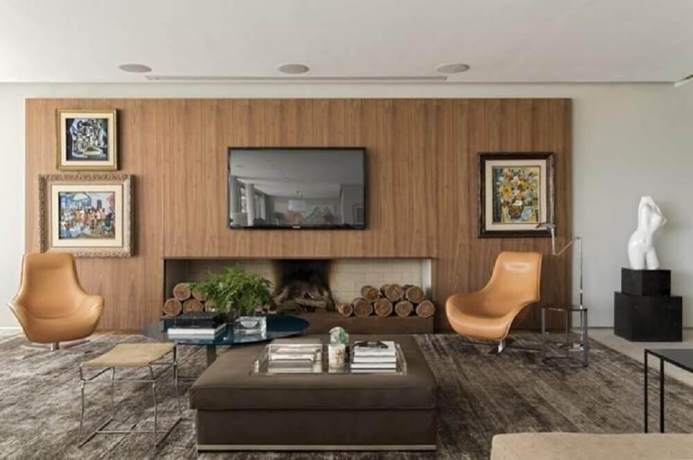 sala de estar com lareira a lenha e parede com revestimento de madeira