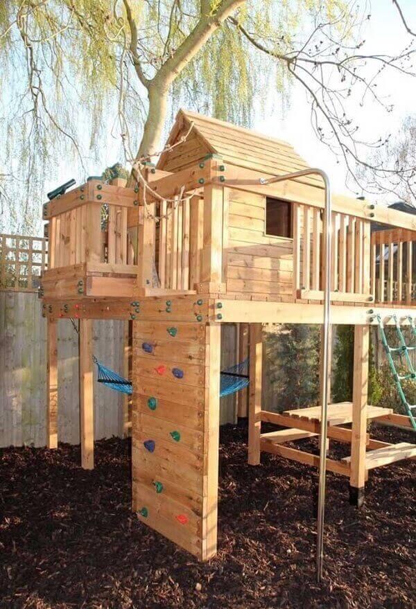 Modelo de casa na árvore com paredão de escalada e rede de descanso