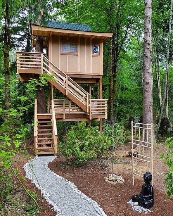 Os troncos passam pela lateral da casa na árvore