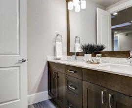 Armário de banheiro feita em madeira escura e bancada branca.