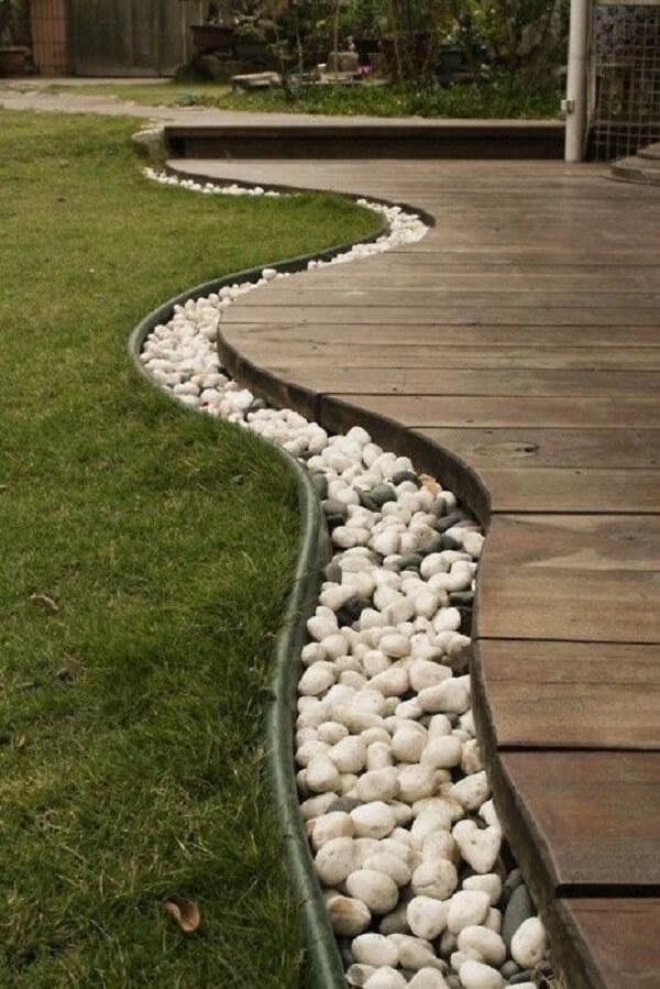 As pedras para jardim contornam todo o deck de madeira