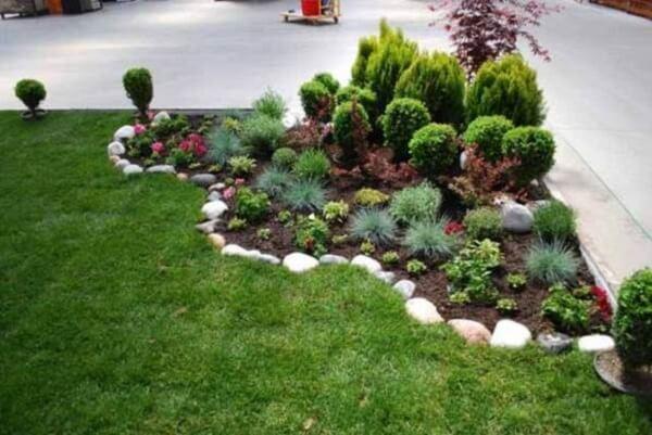 As pedras para jardim delimitam o espaço das plantas no quintal