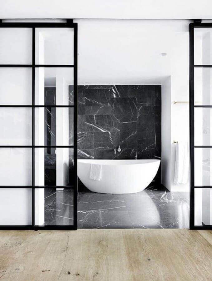 Banheiro decorado moderno com mármore preto e banheira branca - Foto space cph