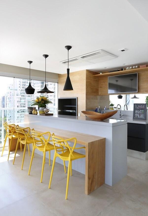Banquetas para cozinha amarelas com encosto alto, bancada de madeira e três luminárias pretas baixas