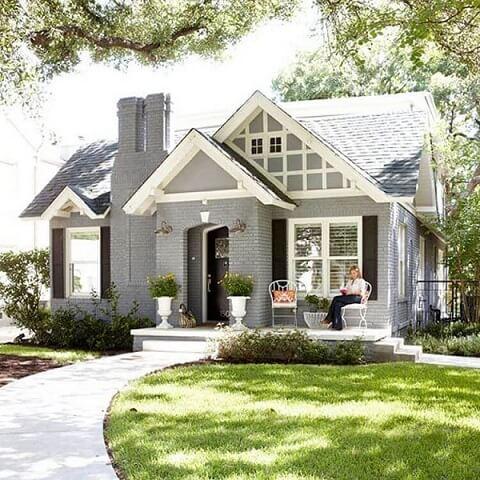 Casa de alvenaria cinza com tijolos expostos