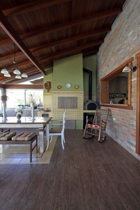 Casa de alvenaria com parede de tijolos à vista e piso de madeira Projeto de Graça Brenner