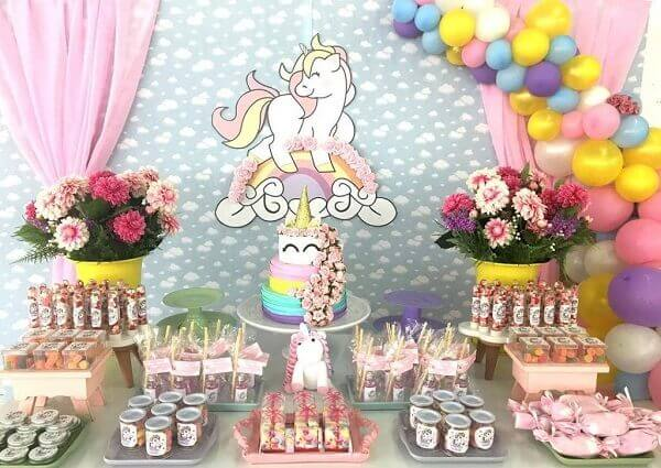 Festa de unicórnio com vários enfeites coloridos na mesa