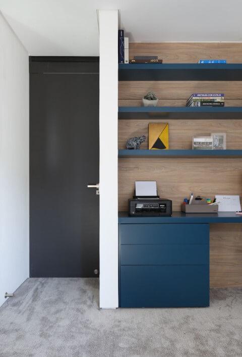 Gaveteiro azul combinando com a mesa e as prateleiras o escritório Projeto de Start Arquitetura