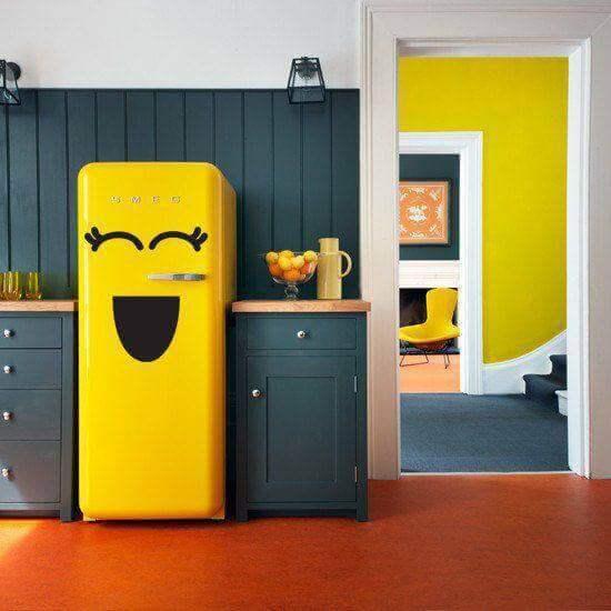 Geladeira adesivada amarela com desenho de emoticon feliz