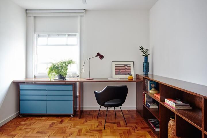 Home office branco com gaveteiro azul sob mesa de madeira Projeto de Iná Arquitetura