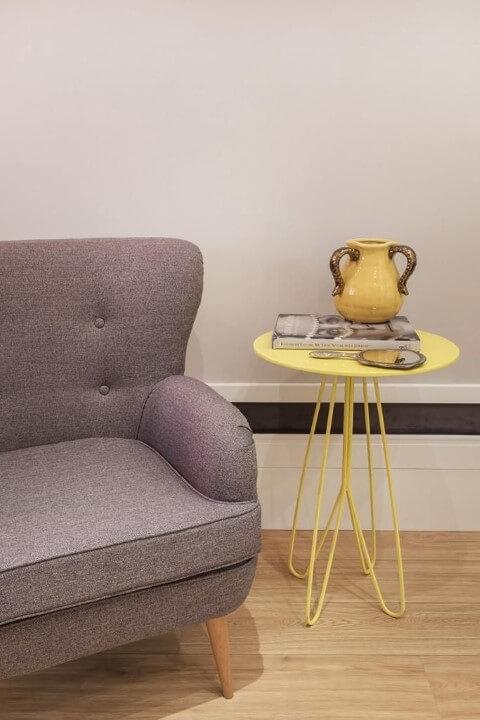 Mesa lateral amarela ao lado de poltrona cinza Projeto de Urbano Studio
