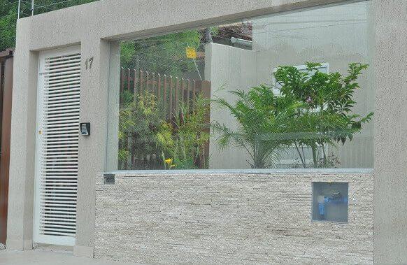 Muros de casas com vidro e pedra canjiquinha