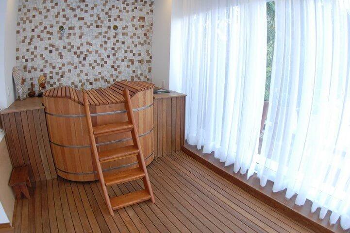 Ofurô de madeira em ambiente interno com deck de madeira Projeto de Monica Spada Durante