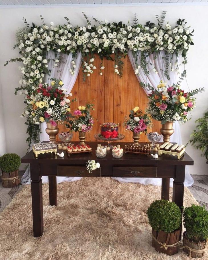 Painel de flores com painel de madeira e cortina branca