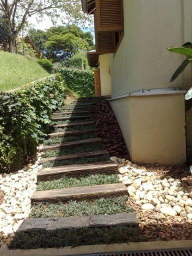 Pedras para jardim em volta de caminho de madeira Projeto de Jader Nunes
