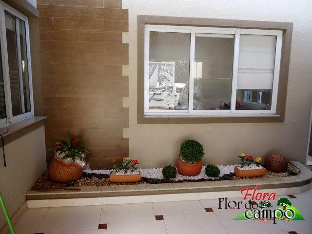 Pedras para jardim no canteiro com vasos de barro Projeto de Flora Flor do Campo