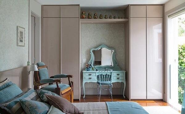 quarto de casal com penteadeira, poltrona e roupa de cama em tons de azul