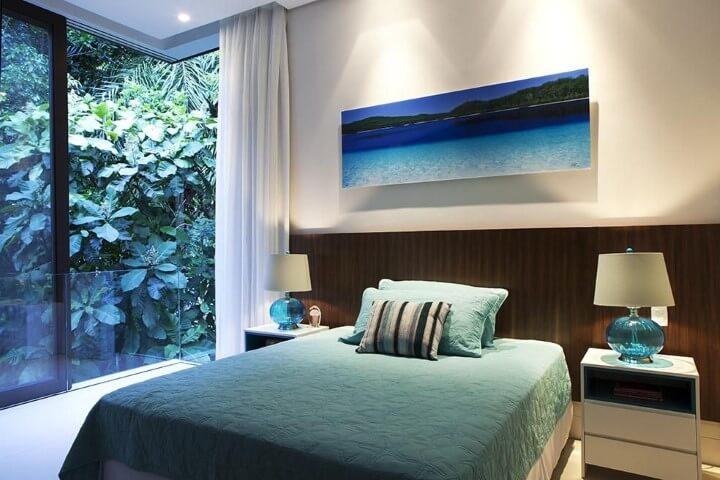 Quarto de solteiro com quadro e roupa de cama em tons de azul turquesa Projeto de Infinity Spaces