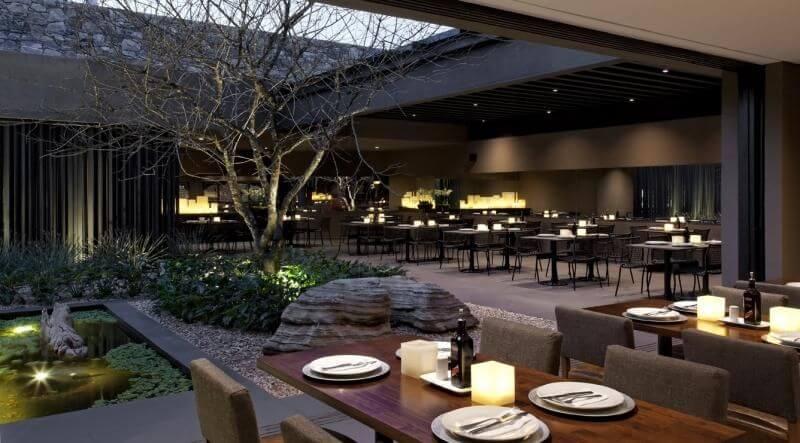 Restaurante com pedras para jardim de inverno aberto Projeto de Roberto Migotto