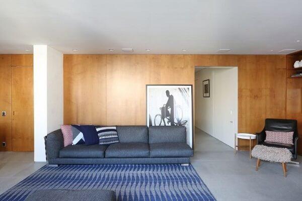 tapete em tons de azul em sala com paredes revestidas de madeira