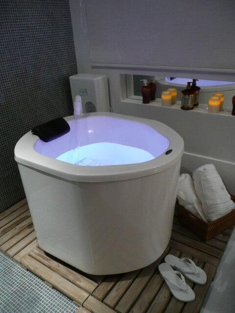 Sala de banho com ofurô com luzes internas e piso de madeira Projeto de Nathalia Alberoni