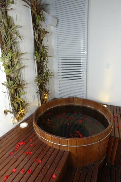 Sala de banho com ofurô e deck de madeira Projeto de Ana Meirelles