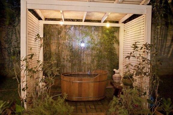 Sala de banho externa com ofurô de madeira Projeto de Cactus Arquitetura