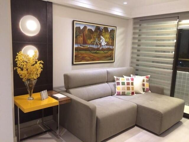Sala de estar com mesa lateral amarela com parte de madeira Projeto de Caroline Guerra