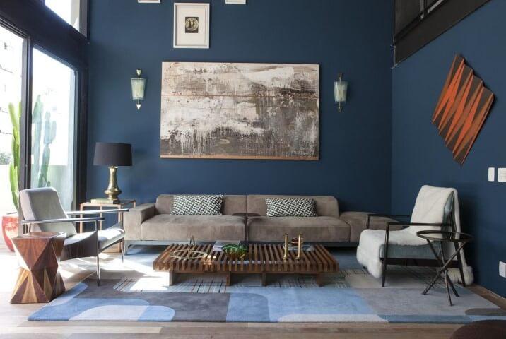 Sala de estar com parede e móveis em tons de azul Projeto de AMC Arquitetura